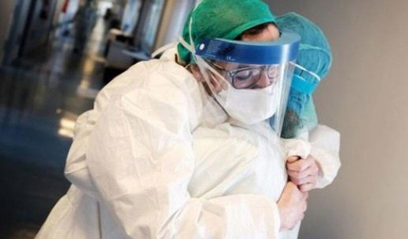 Sebagai ilustrasi: Tenaga medis pasien virus corona di Italia berpelukan untuk saling menguatkan. [Paolo Miranda/BBC]